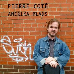 Le musicien devant un mur de brique et appuyé sur son étui de guitare