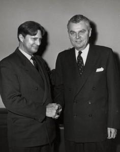 Pier Paquette dans le rôle du Maire Rosaire Groulx qui serre la main du premier ministre John Diefenbaker en 1958.