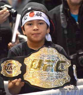 Un jeune fan de GSP avec la réplique de la ceinture de l'UFC