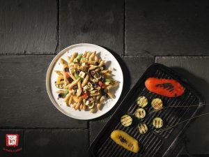 Pennes de blé entier aux légumes grillés : olives Kalamata, aubergines sur le grill, poivrons aux couleurs de l'arc-en-ciel, jolies courgettes, le tout nappé de fromage féta et d'une sauce fraiche aux tomates californiennes garnie d'un pesto maison au basilic du jardin